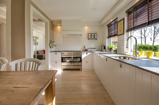 A kitchen with wooden cabinets and a dining table